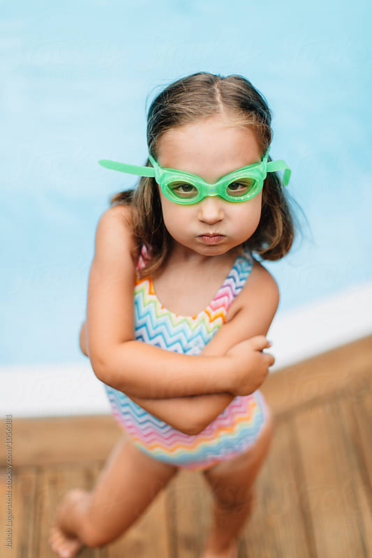 Portrait of a cute and sassy girl in swim goggles standing by a pool by Jakob for Stocksy United