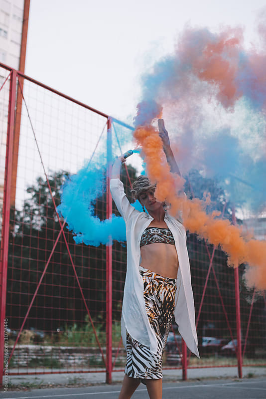 Woman Holding Two Smoke Bombs by Mosuno for Stocksy United