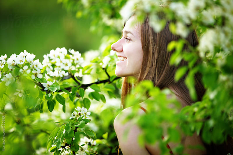 Young woman enjoying spring blossom by Ilya for Stocksy United