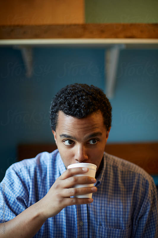 Close up of young man drinking a hot chocolate in his business by Miquel Llonch for Stocksy United