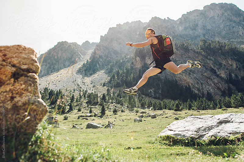 Young sporty hiker jumping over rocks   by Jordi Rulló for Stocksy United