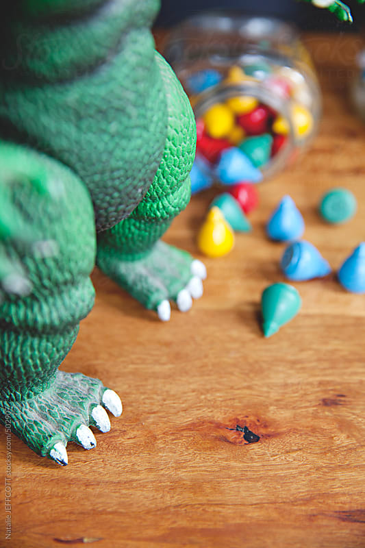 close up of vintage dinosaur feet and toys in a jar on a desktop by Natalie JEFFCOTT for Stocksy United