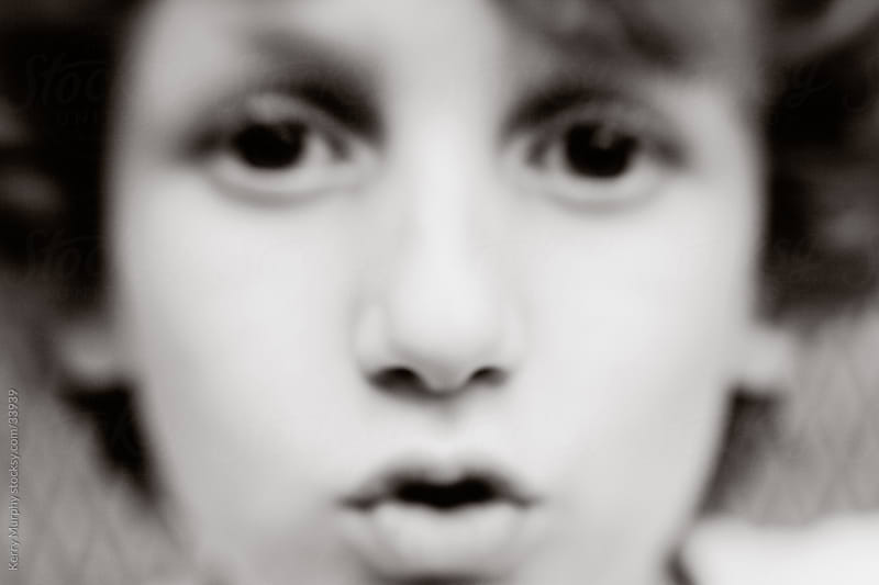 Black and white closeup of young boy's face by Kerry Murphy for Stocksy United
