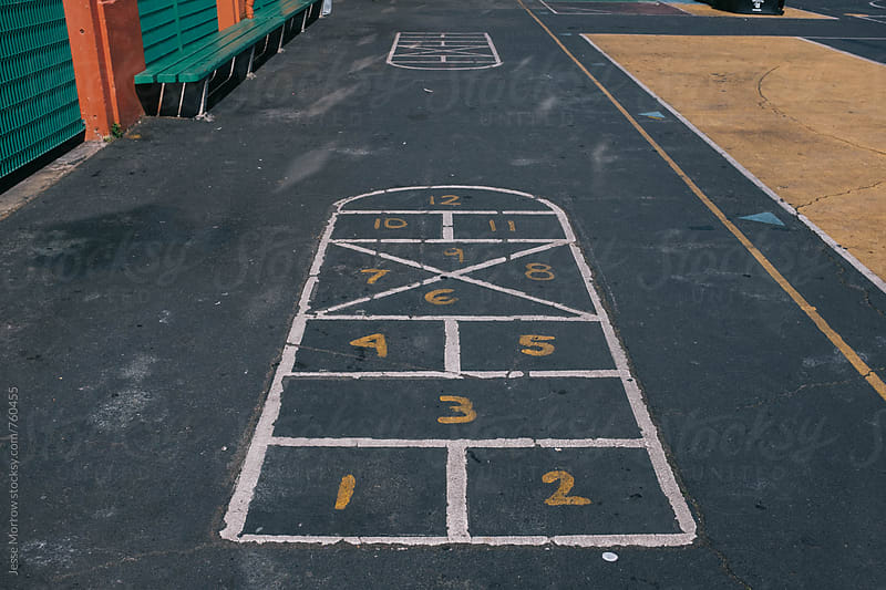 learn numbers and hop-scotch painted on concrete on playground by Jesse Morrow for Stocksy United