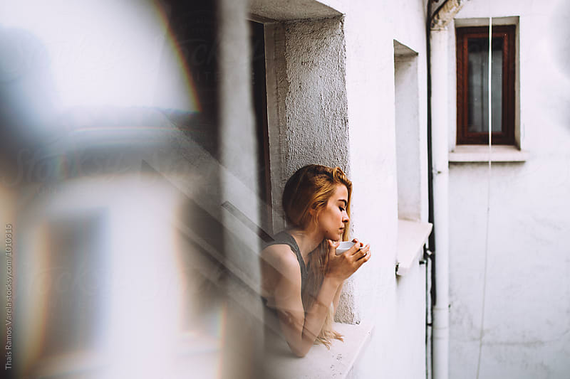 portrait of a woman at the window by Thais Ramos Varela for Stocksy United