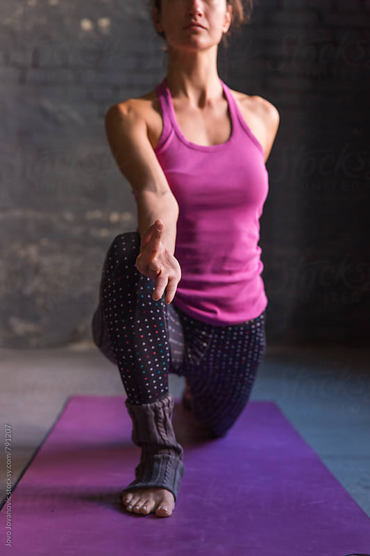 Young woman extending an arm forward in a yoga pose  by Jovo Jovanovic for Stocksy United