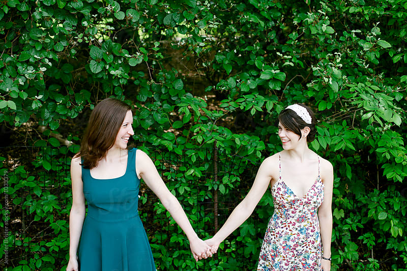 Two women holding hands in park by Jen Brister for Stocksy United