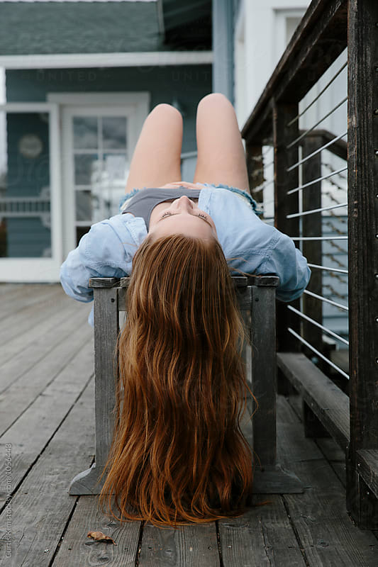 Woman with red hair laying down on bench by Curtis Kim for Stocksy United
