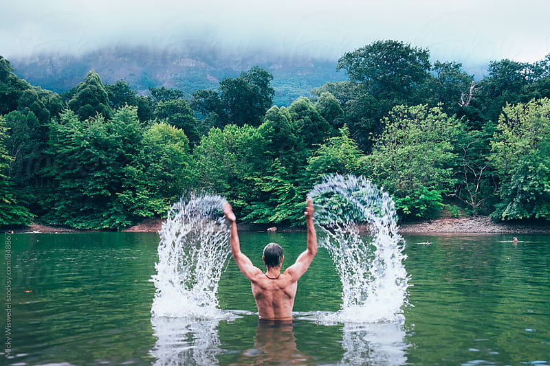 Man swimming in a forest lake by Micky Wiswedel for Stocksy United