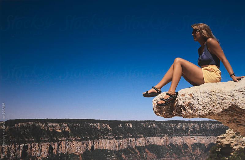 Girl sitting on rock ledge overlooking the Grand canyon. by Soren Egeberg for Stocksy United
