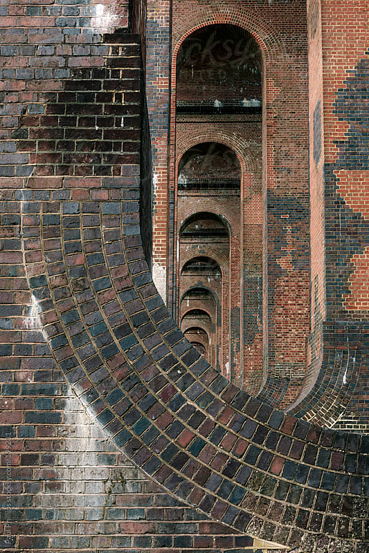 Curved receding interior arched columns of a railway viaduct by Paul Phillips for Stocksy United