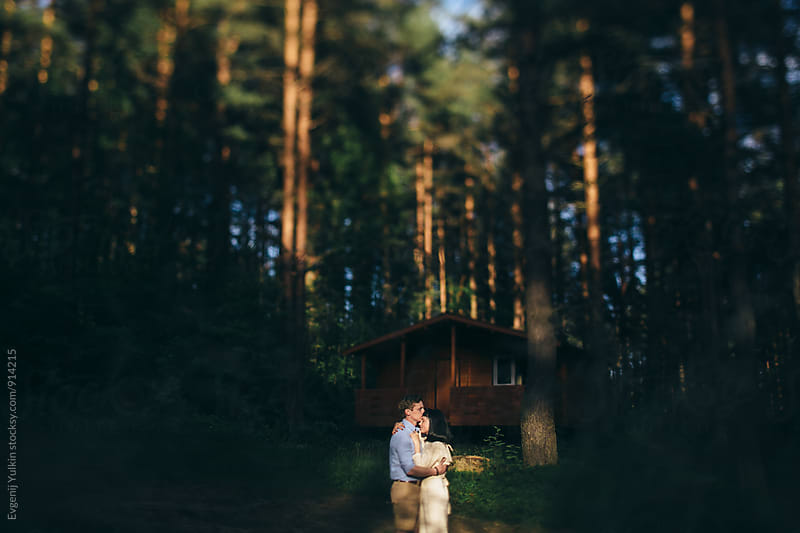 Young couple embracing in the spotlight in the forest by Evgenij Yulkin for Stocksy United