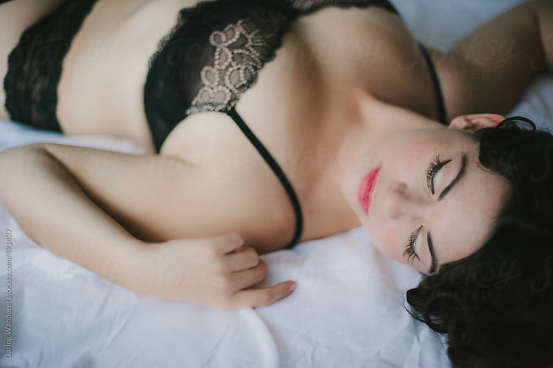 Woman in black lace bra lying on bed by Daring Wanderer for Stocksy United