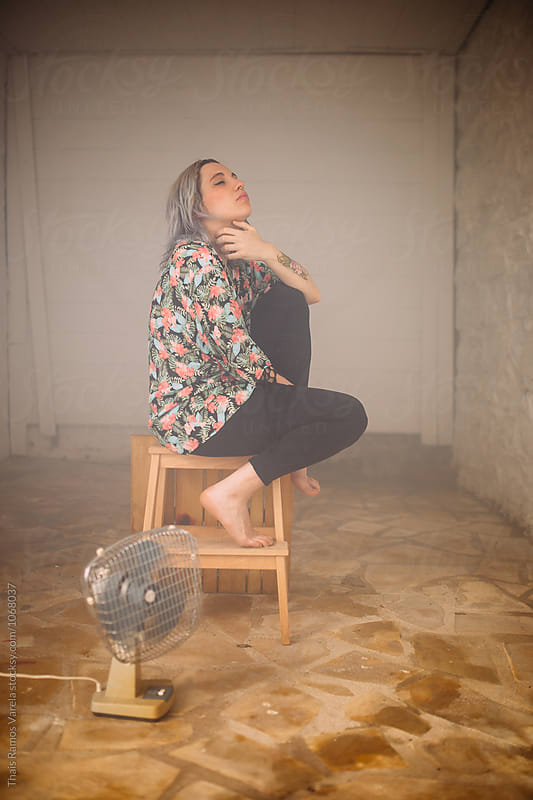 woman sitting in a foggy room by Thais Ramos Varela for Stocksy United