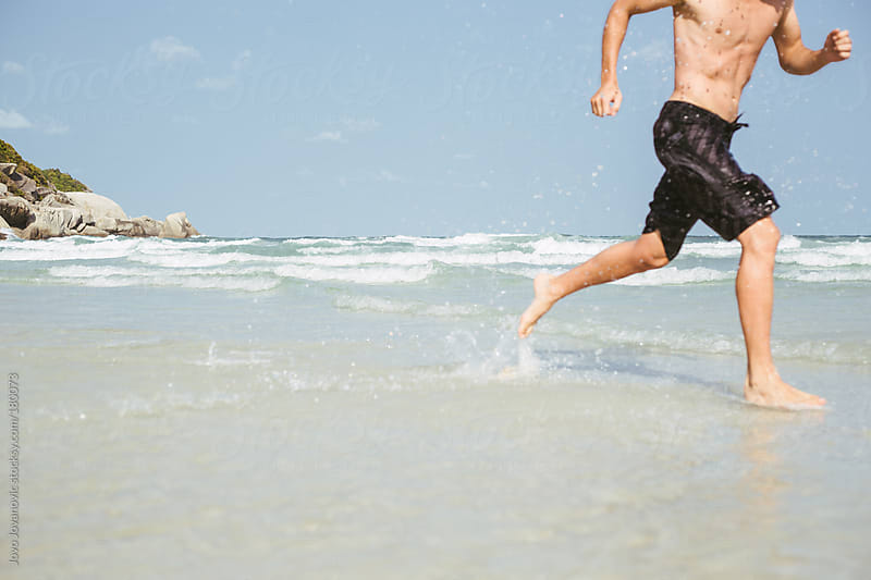 Physically fit man running alone on a beach by Jovo Jovanovic for Stocksy United
