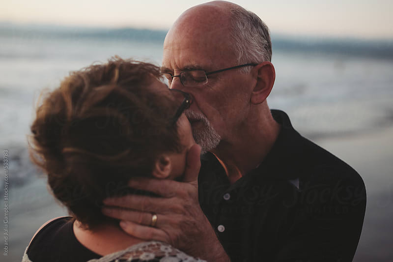 Romantic middle aged, retired couple kiss together outside on ocean beach by Rob and Julia Campbell for Stocksy United