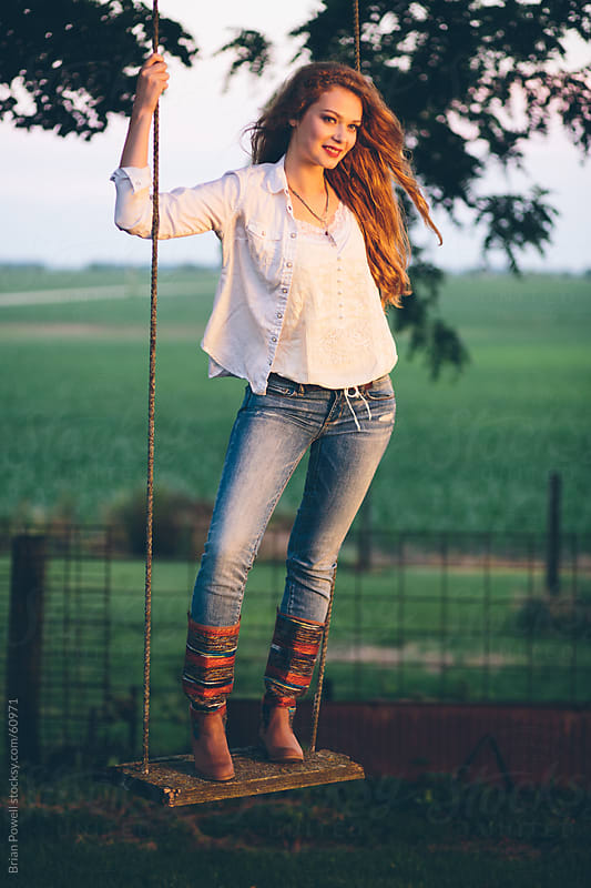 young woman standing on wooden swing by Brian Powell for Stocksy United