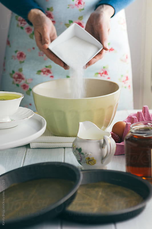 Woman adding sugar into mixing bowl to make chocolate cake by Kirsty Begg for Stocksy United