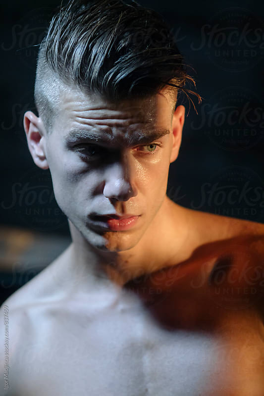 Contrast moonlight and light bulb , portrait of a handsome fashionable young man , stylish haircut by Igor Madjinca for Stocksy United