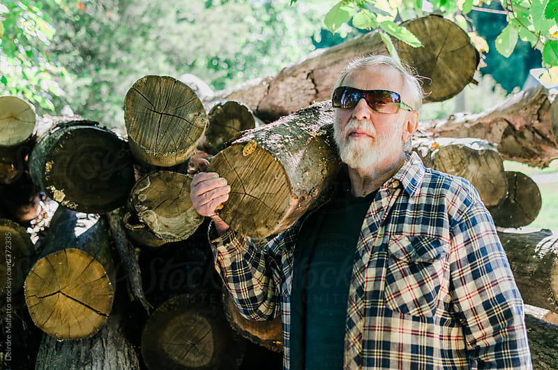A man with his logs by Deirdre Malfatto for Stocksy United