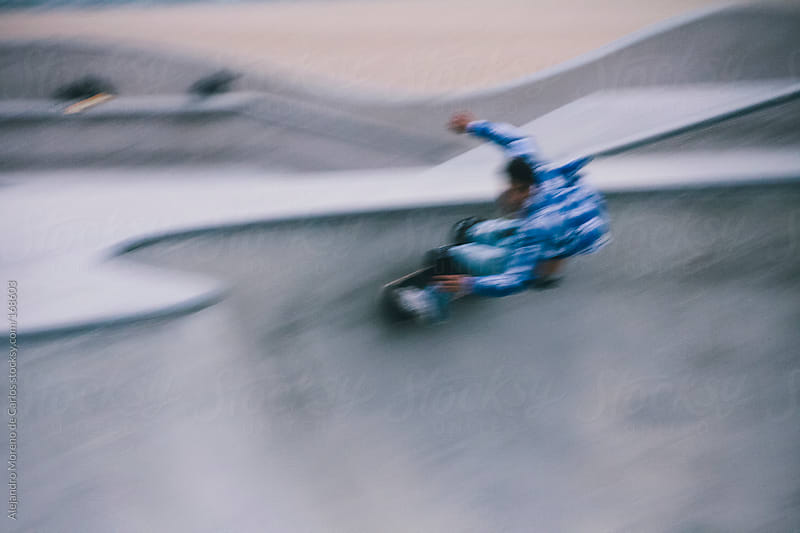 Skater riding skateboard on a bowl. Speed blurred image by Alejandro Moreno de Carlos for Stocksy United