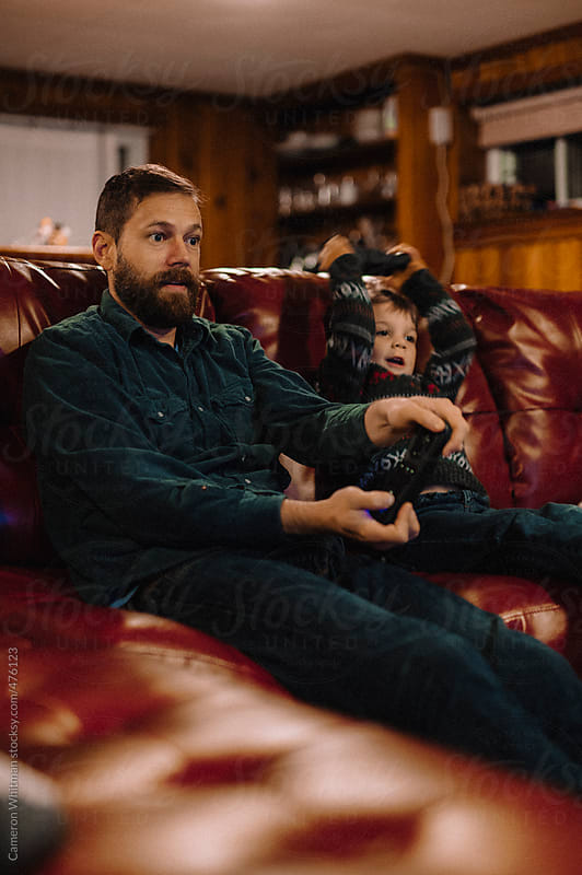 Father and Son playing video games by Cameron Whitman for Stocksy United