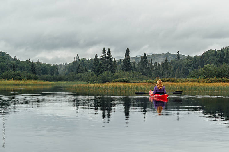 Woman kayaking on calm remote lake by Preappy for Stocksy United