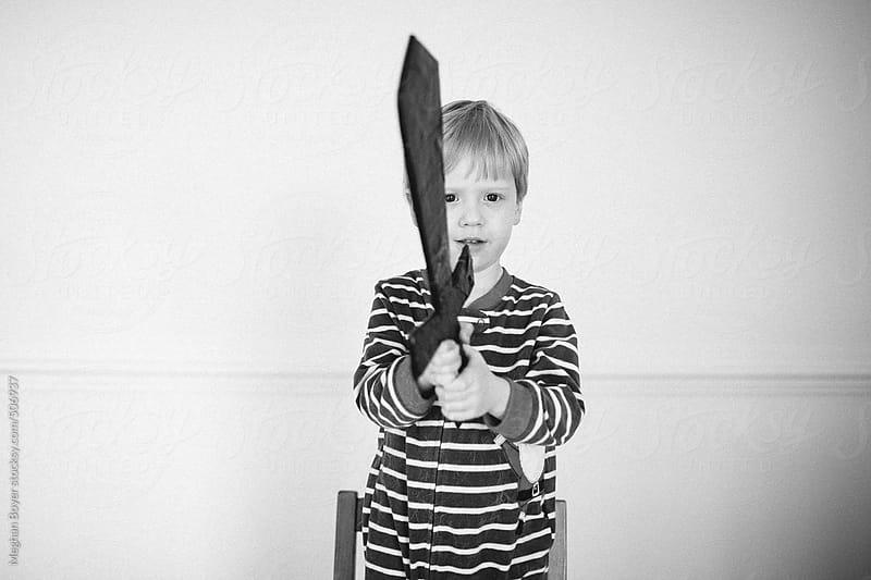 boy playing with a cardboard sword by Meghan Boyer for Stocksy United