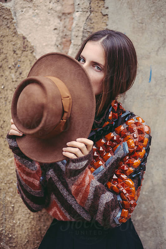Woman wearing colorful clothes and a hat in front of a vintage wall by Maja Topcagic for Stocksy United