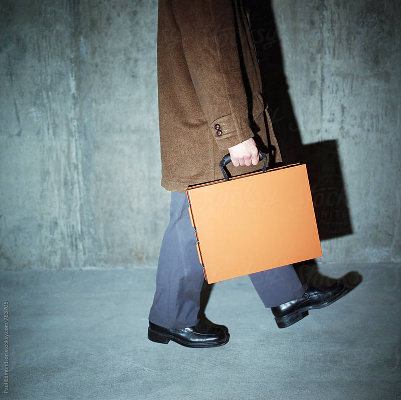 Businessman walking and holding metal briefcase by Paul Edmondson for Stocksy United