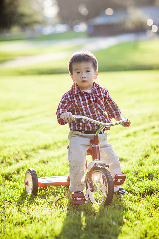 Asian kid riding a tricyle outdoor by Suprijono Suharjoto for Stocksy United
