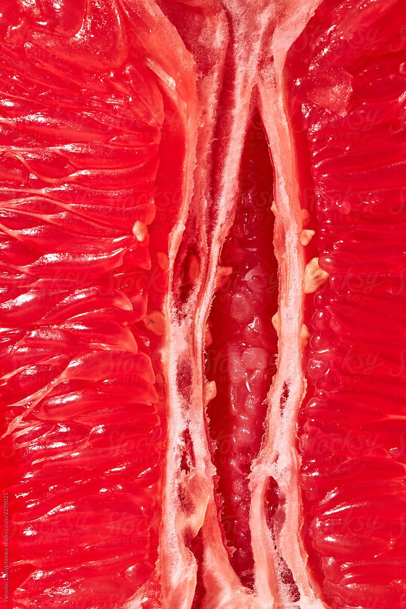 Macro view of cut ripe fresh grapefruit. Close-up of vagina symbol  background.