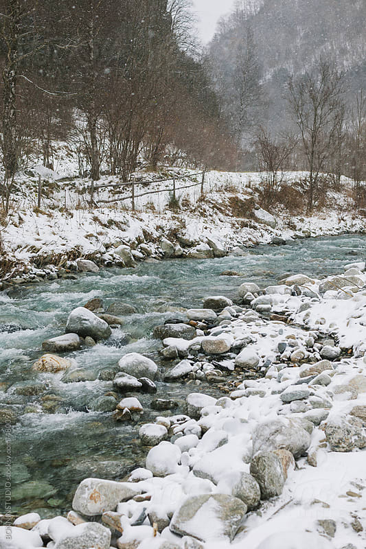 River on a snowy landscape.  by BONNINSTUDIO for Stocksy United
