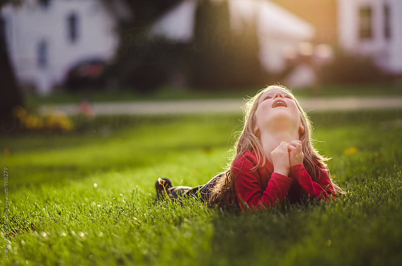 Young girl lying on the grass and looking up by Lindsay Crandall for Stocksy United