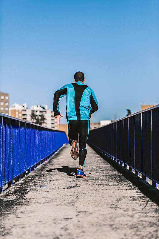 Man Running on a Bridge Over Road by VICTOR TORRES for Stocksy United