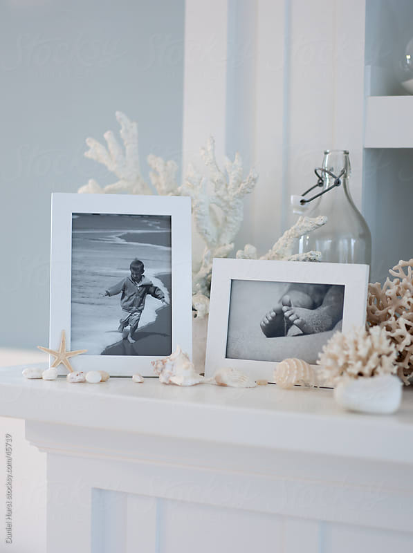 Family photos and coastal objects on ledge by Daniel Hurst for Stocksy United