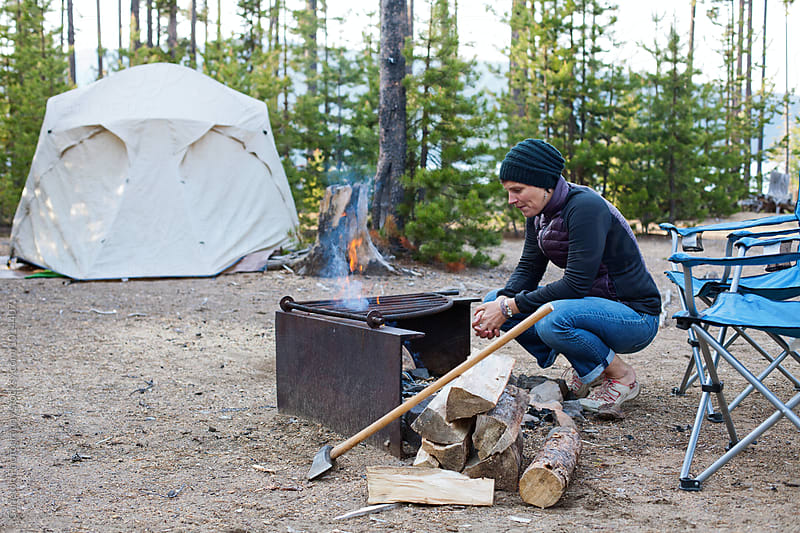 Woman warms her hands by the campfire by Carleton Photography for Stocksy United