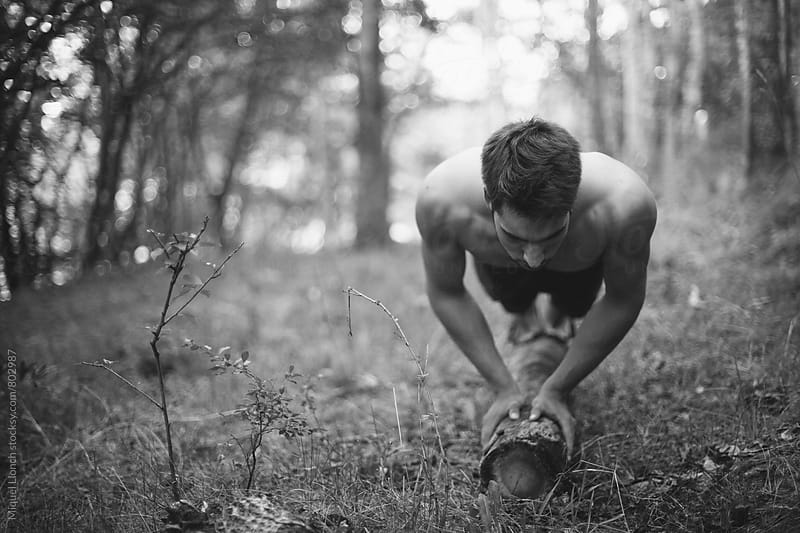 Young man doing push-ups with a log in the nature by Miquel Llonch for Stocksy United