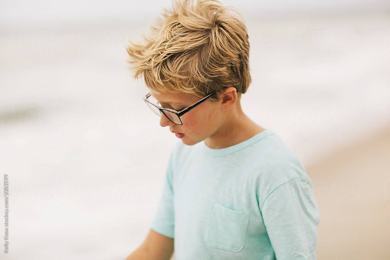boy with wind blown hair by the ocean by Kelly Knox for Stocksy United