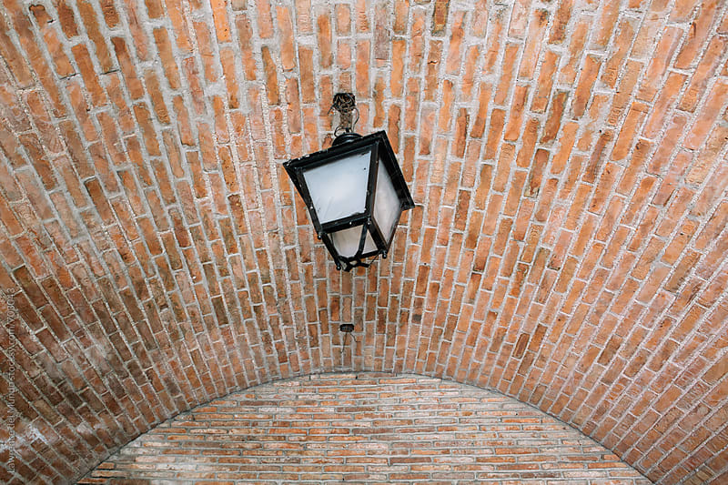 Lamp light on a red brick ceiling of a horse carriage stall  by Lawrence del Mundo for Stocksy United