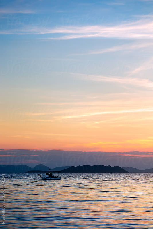 Sunset with Small Boat Seascape by Helen Sotiriadis for Stocksy United