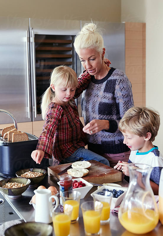Mom and kids making breakfast in the morning in the kitchen  by Trinette Reed for Stocksy United