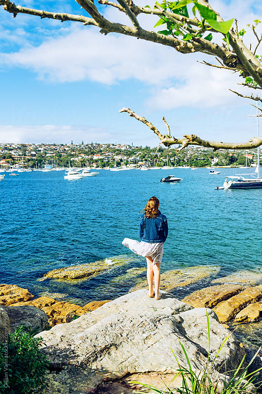 Sydney Harbour, a teenager stands on rocks in a small cove looking at the yachts and big homes by Gillian Vann for Stocksy United