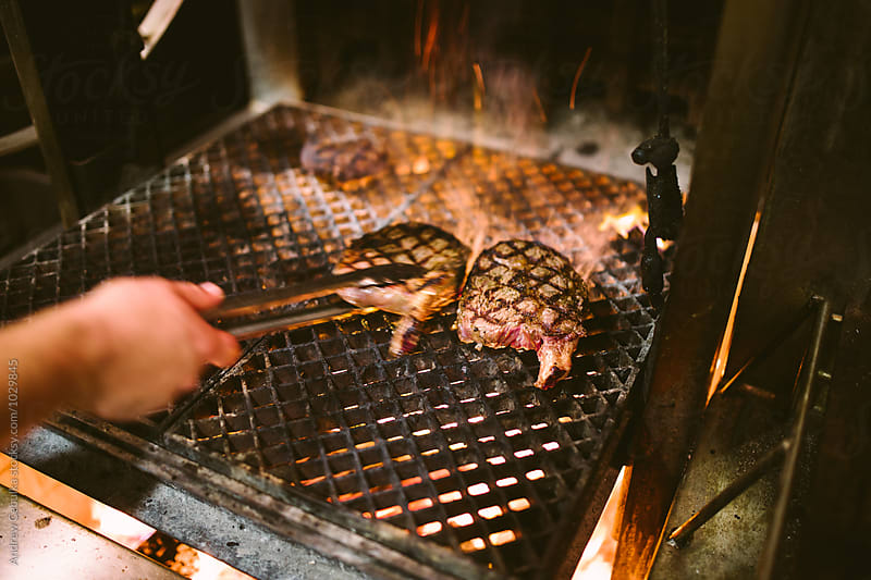 grilling bone in ribeye over open flame grill by Andrew Cebulka for Stocksy United