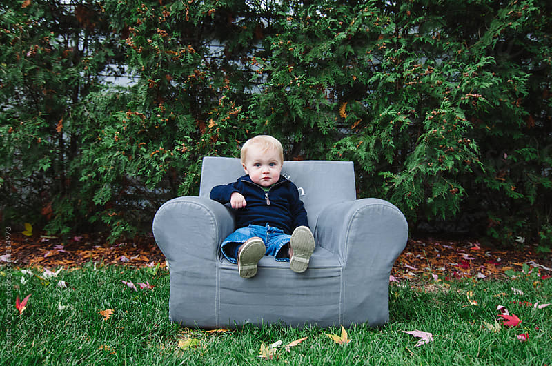little boy sits in mini armchair by Margaret Vincent for Stocksy United