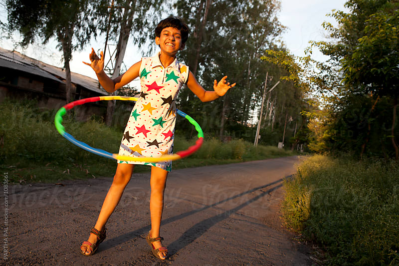 Teenage girl making fun with Hula hoop by PARTHA PAL for Stocksy United