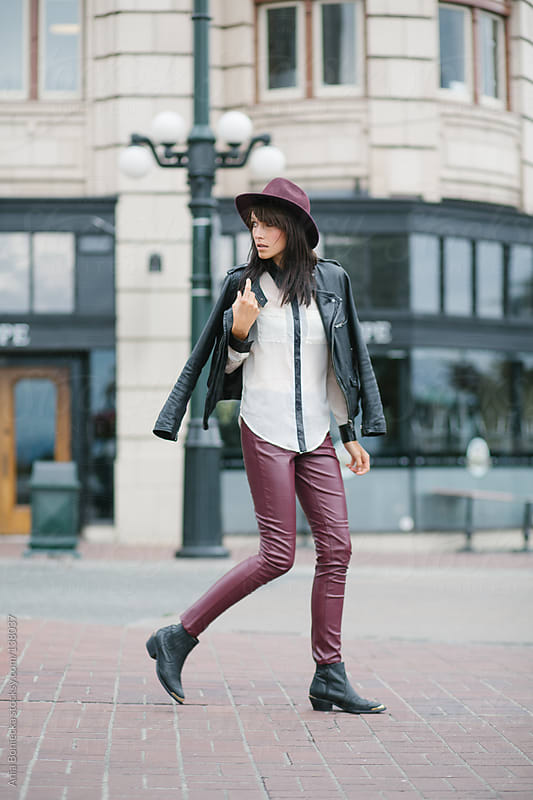 A trendy girl dressed in leather walking and looking back by Ania Boniecka for Stocksy United