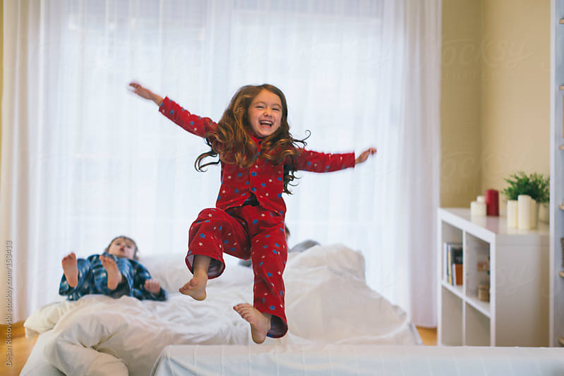 Children jumping on a bed by Dejan Ristovski for Stocksy United
