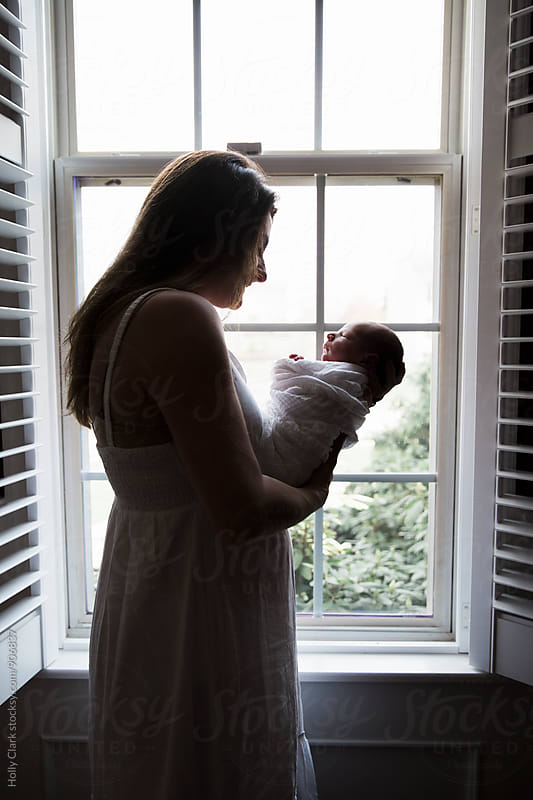 Mother holding her newborn son by Holly Clark for Stocksy United