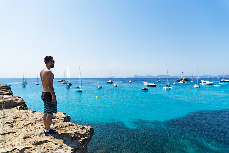 Young man looking at paradise beach in Mediterranean Sea by ACALU Studio for Stocksy United